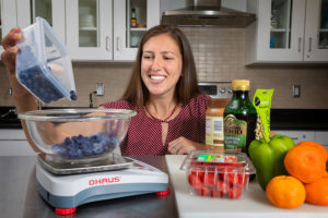 Dr. Claire Berryman in a nutrition lab dumping blue berries from a plastic container onto a food scale