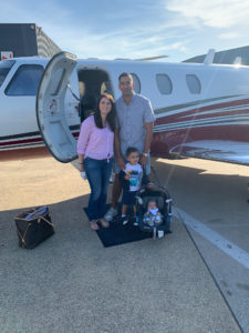 Suresh Narayanan posing with his family outside of a private plane